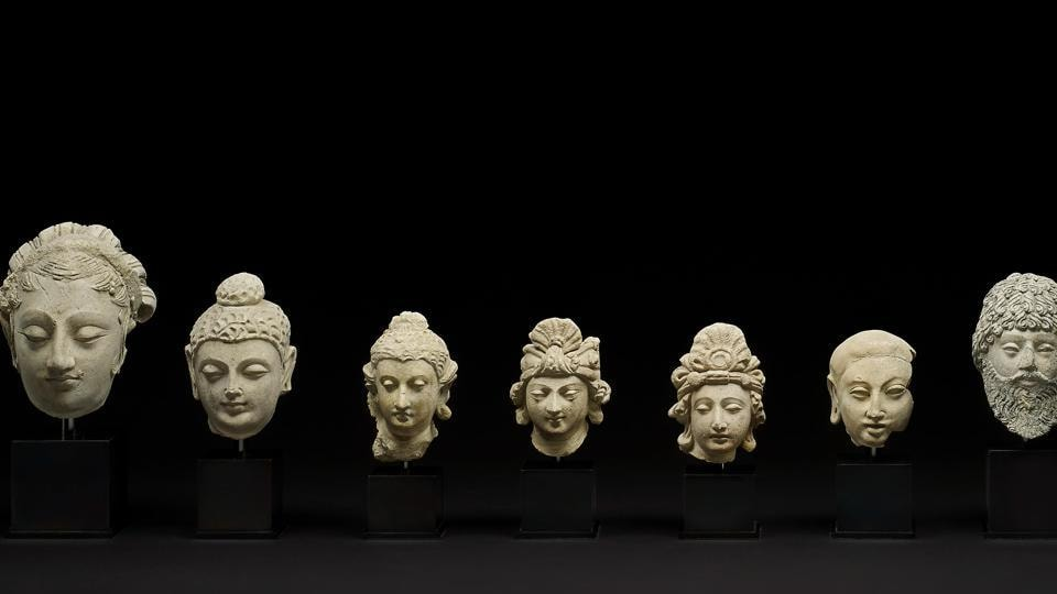 The items include a portrayal of Buddha, the turbaned heads of meditating Bodhisattvas, the bald head of a monk and three larger heads belonging to female and male individuals, one possibly to be identified with Vajrapani, the spiritual guide of Buddha, and the others perhaps lay donors or Bodhisattvas.
