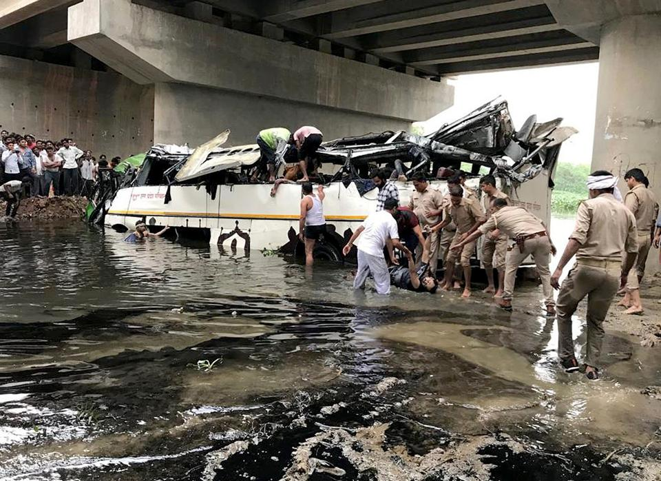 Rescue workers and policemen trying to recover the bodies of dead and injured from the mangled remains of UP Roadways  bus after it fell off the Yamuna Expressway into a large drain near Agra on Monday, July 8, 2019.
