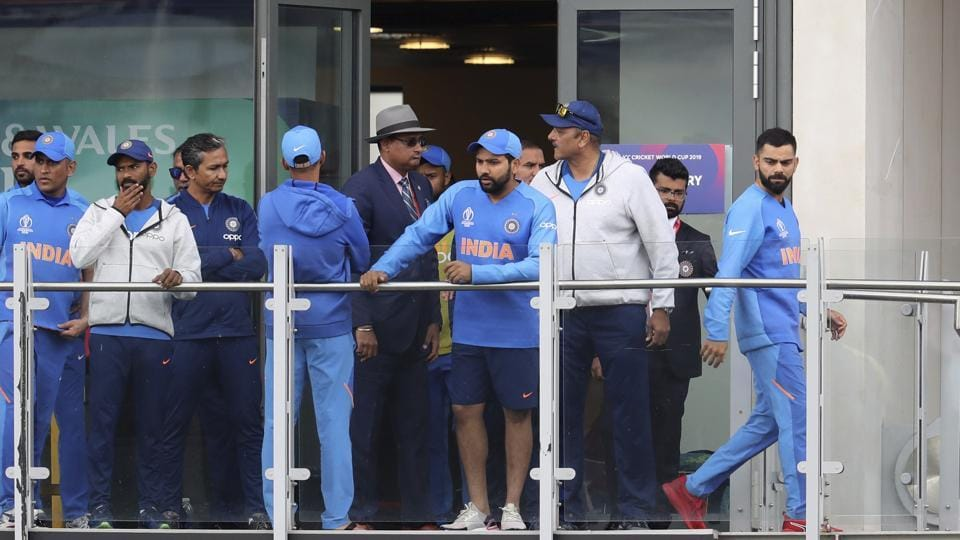 India's captain Virat Kohli, right, stands in the pavilion with teammates.