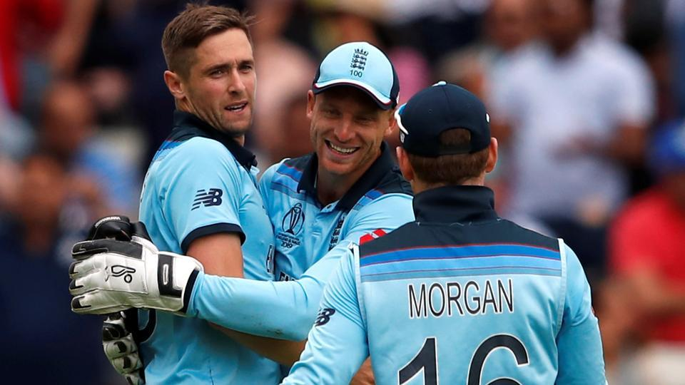 England's Chris Woakes and Jos Buttler celebrate taking the wicket of Australia's Mitchell Starc.