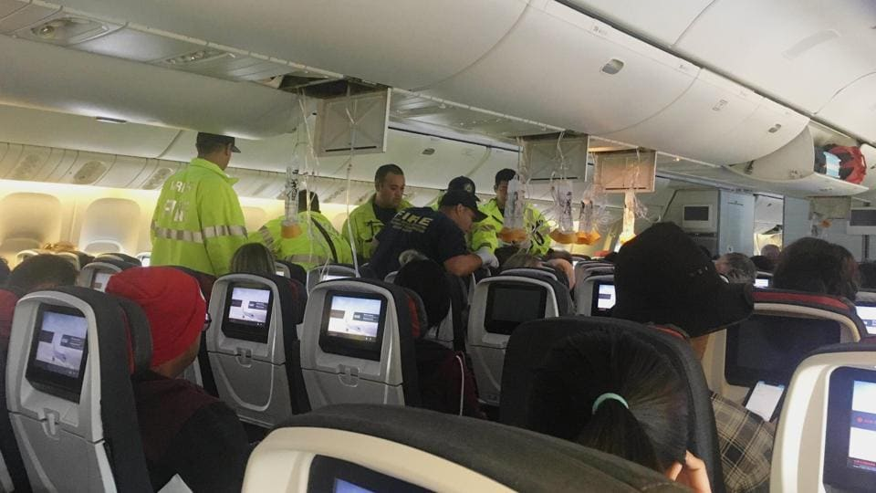 In this photo provided by Hurricane Fall, responders treat a passenger on an Air Canada flight to Australia that was diverted and landed at Daniel K. Inouye International Airport in Honolulu on Thursday, July 11, 2019. The flight from Vancouver to Sydney encountered