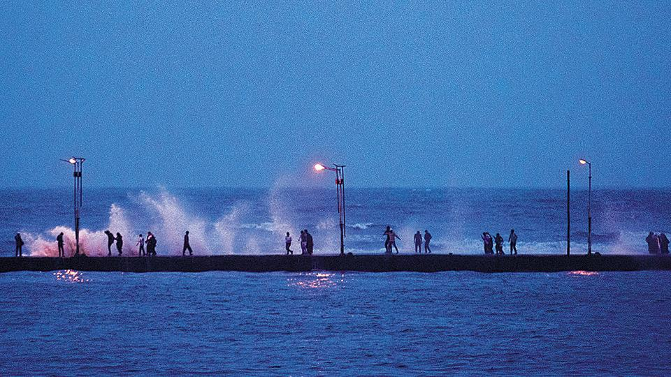 People walk towards the Haji Ali Dargah during high tide on Thursday. The weather department has predicted light to moderate rain until next week.