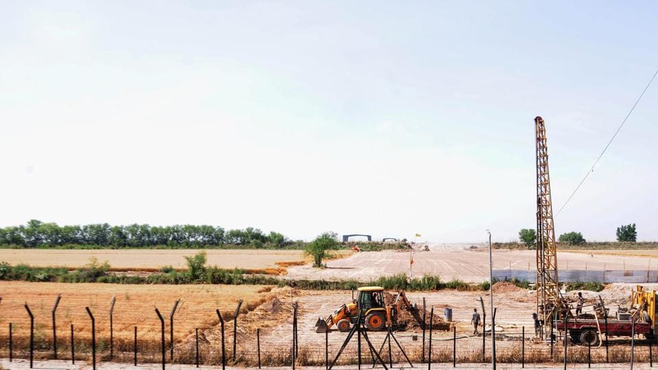 Machines at work beyond the border fence for the construction of the Indian side of Kartarpur corridor, in Gurdaspur district.
