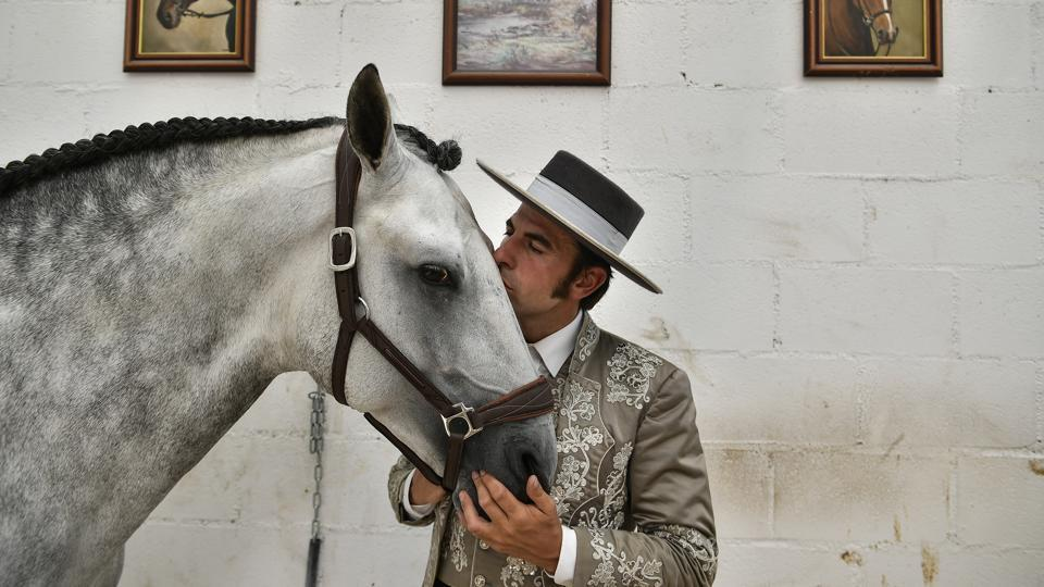 """Roberto Armendariz, 33, a Spanish """"rejoneador'' or mounted bullfighter, poses with one of his horses called Heroi, at his ranch in Noain, northern Spain. Of all traditions surrounding the varied world of bullfighting, the horse mounted """"rejoneo"""" bullfighting is among the least understood. Fans consider it a skilled art form; others see it as a cruel and bloody crime for the sake of entertainment. (Alvaro Barrientos / AP)"""