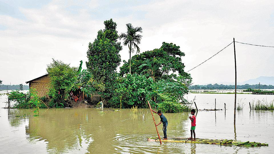 Children paddle a raft through flood waters in Murkata village of Morigoan district in Assam, on July 12, 2019.