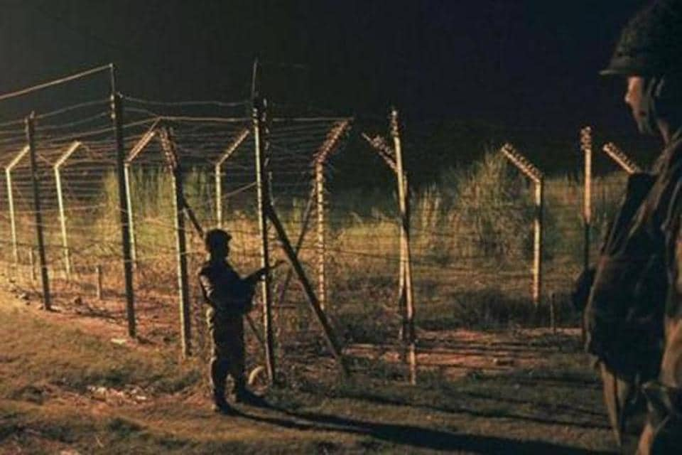 Border Security Force (BSF) soldiers standing guard during a night patrol near the fence at the India-Pakistan International Border at the outpost of Akhnoor sector.