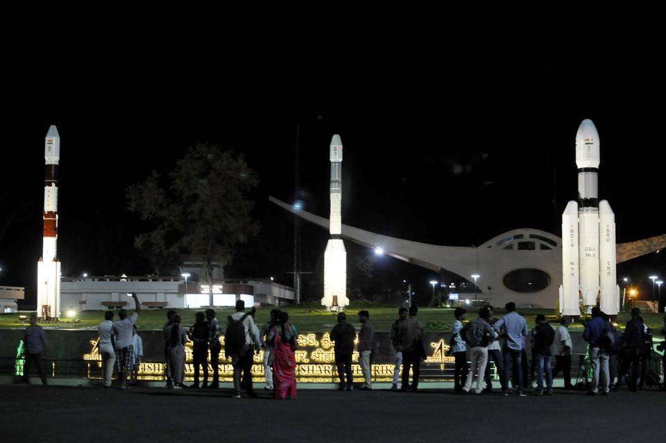 People standing next to models of Indian Space Research Organization (ISRO)'s Geosynchronous Satellite launch Vehicle (GSLV) MkII at Satish Dhawan Space Center after the Chandrayaan-2 mission was aborted from Sriharikota on Sunday.