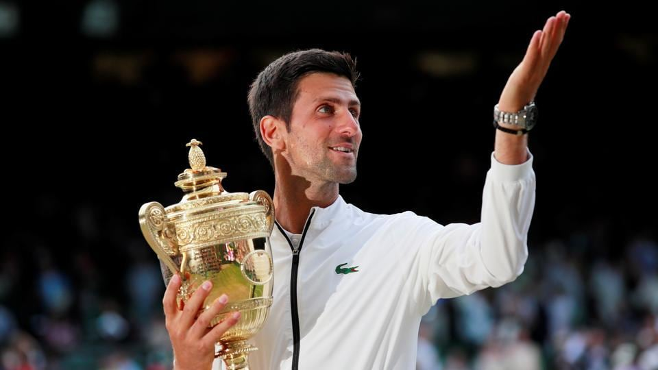 Novak Djokovic poses with the trophy as he celebrates winning the final against Roger Federer.