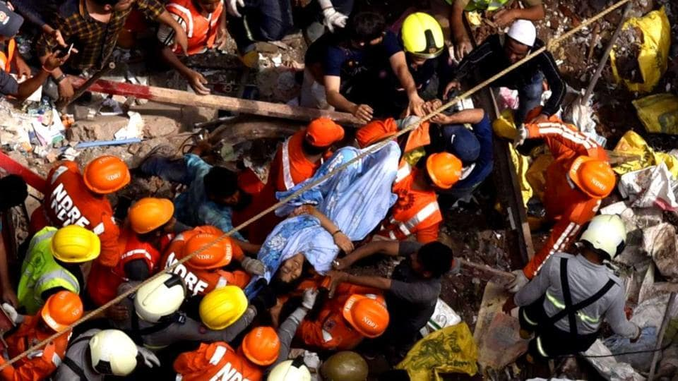 Indian National Disaster Response Force and Indian fire brigade personnel rescue a survivor from after a building collapsed in Mumbai on July 16, 2019.