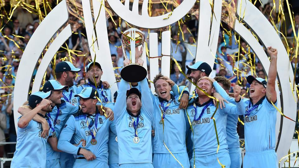 England's captain Eoin Morgan lifts the World Cup trophy as England's players celebrate their win.