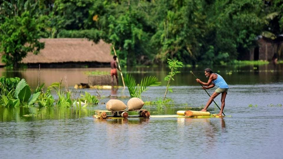 A man uses a makeshift raft to move his paddy to a safer place in a flooded area in Assam's Morigaon district .