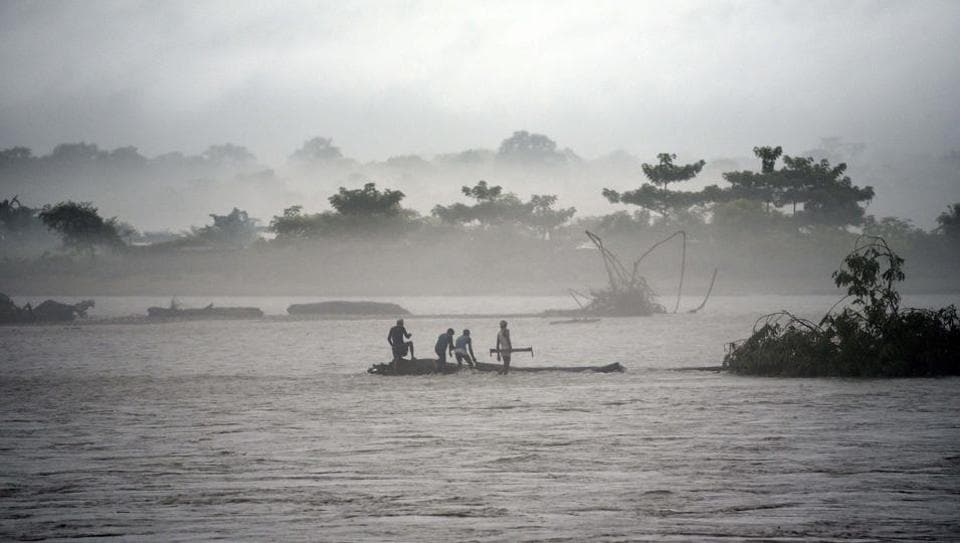 Men clear a tree from the flooded Manas river, following heavy rainfall in Baksa district of Assam. Heavy rainfall has submerged 30 of the 33 districts in the state. The death toll has reached 15 so far. As residents struggle to shift to safer places, rescue operations are underway to manage the calamity. (David Talukdar / AFP)