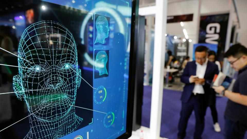 Visitors check their phones behind the screen advertising facial recognition software during Global Mobile Internet Conference (at the National Convention, Beijing, China, 2018