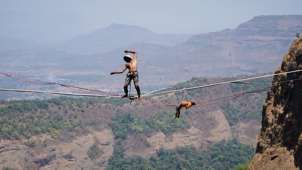 Samar Farooqui performs highlining at Duke's Nose, Lonavala, in Mumbai. 28-year-old Farooqui, who studied adventure tourism, was introduced to the sport by a friend in 2010 and since then he has become the pioneer for slacklining in India. Slacklining refers to the act of walking or balancing along a suspended length of flat webbing that is tensioned between two anchors. (Hemanshi Kamani / HT Photo)