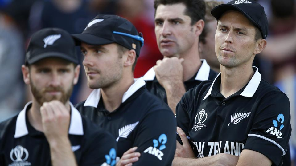 New Zealand's Trent Boult, right, crosses his arms as he waits for the trophy presentation after losing the Cricket World Cup final match between England and New Zealand at Lord's cricket ground in London, Sunday, July 14, 2019. England won after a super over after the scores ended tied after 50 overs each. (AP Photo/Matt Dunham)