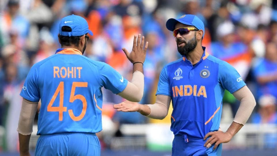 India's captain Virat Kohli (R) celebrates with India's India's Rohit Sharma the wicket of New Zealand's Matt Henry for one during the 2019 Cricket World Cup first semi-final between New Zealand and India at Old Trafford in Manchester, northwest England, on July 10, 2019. (Photo by Dibyangshu Sarkar / AFP) / RESTRICTED TO EDITORIAL USE