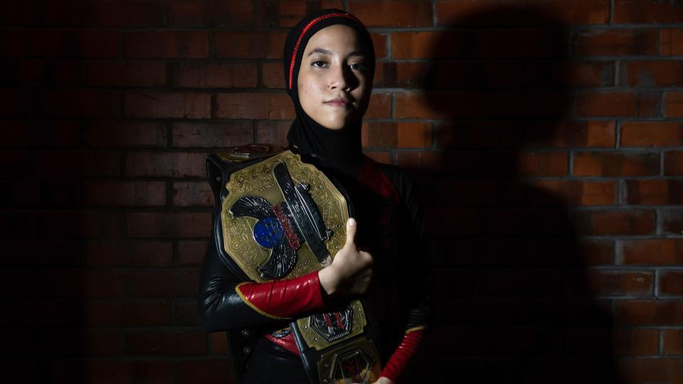 "Diana poses for a picture with the Wrestlecon championship belt. ""As soon as she became popular, we received a lot of messages from fellow hijabis who inquired about joining wrestling as well. She kind of broke the barrier and just proved to them that if she can do it, they can do it too,"" said Ayez Shaukat Fonseka, her coach and fellow fighter.  (Mohd Rasfan / AFP)"