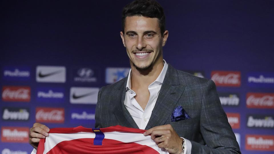 Mario Hermoso holds up his new shirt after signing for Atletico Madrid from Espanyol.