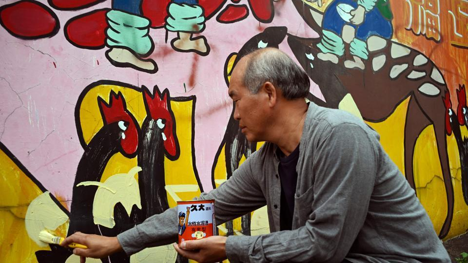 Hakka graffiti artist Wu Tsun-hsien painting a wall in the Taiwanese village of Ruan Chiao.