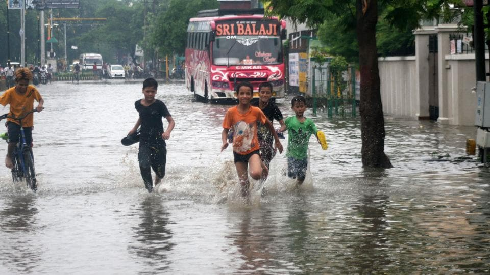 Children play on a water-logged road following heavy monsoon rain in Varanasi, Thursday, July 11, 2019.  A flood alert has been sounded for 15 districts of east UP following heavy rain in the region.