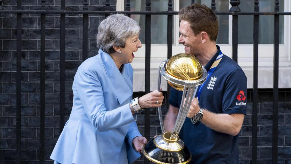 Britain's Prime Minister Theresa May (L) shares a joke with England's captain Eoin Morgan.