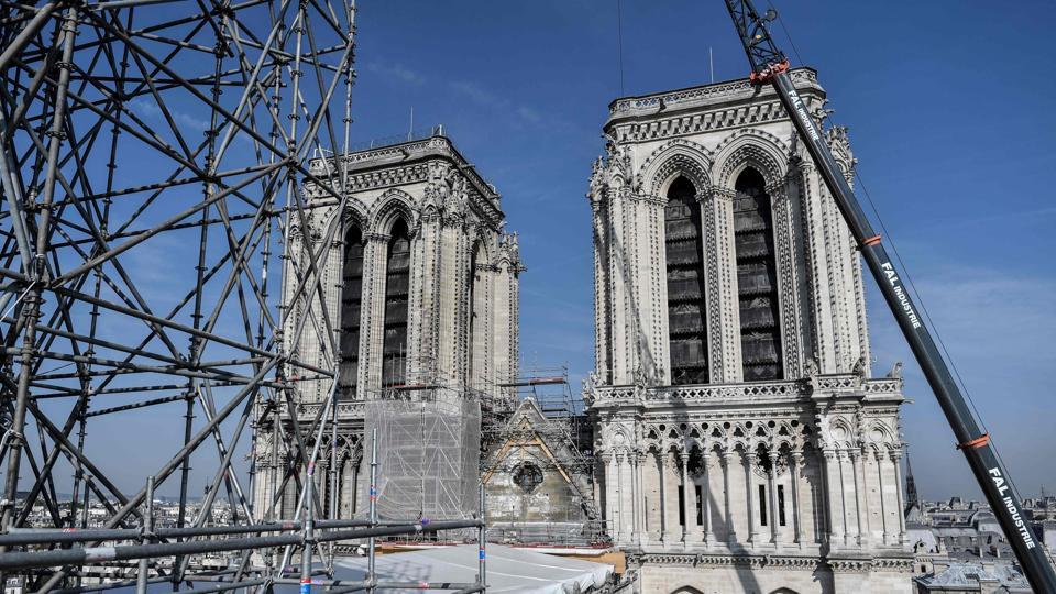 Scaffolding is seen during preliminary work on top of the Notre-Dame de Paris Cathedral after the fire, on July 17, 2019 in Paris, France. Just three months ago, it would have been packed with worshippers and tourists admiring the Gothic architecture and famed stained-glass windows, which emerged largely unscathed from the inferno. (Stephane de Sakutin / Pool / AFP)
