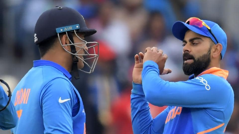 India's captain Virat Kohli (R) speaks with teammate Mahendra Singh Dhoni.