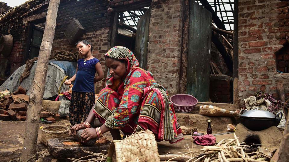 A woman cooks outside her house destroyed by the cyclone
