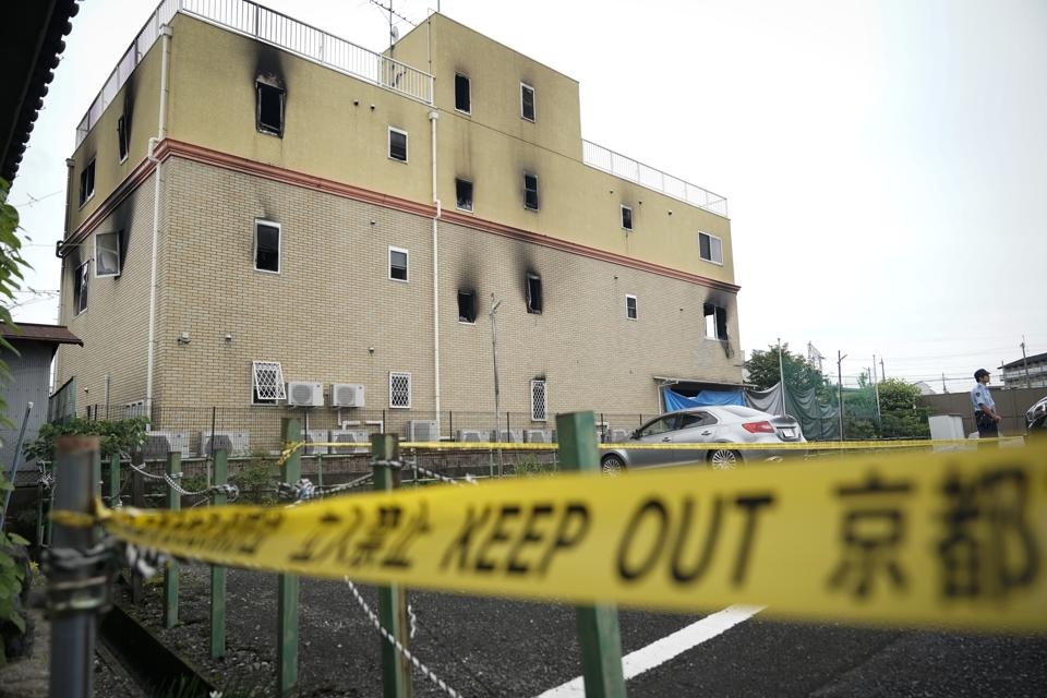 A police officer stands in front of the Kyoto Animation Studio building consumed in an arson attack Saturday on July 20, 2019 in Kyoto, Japan. The man suspected of setting ablaze a beloved Japanese animation studio was raging about theft and witnesses and media reported he had a grudge against the company, as questions arose why such mass killings keep happening in the country.