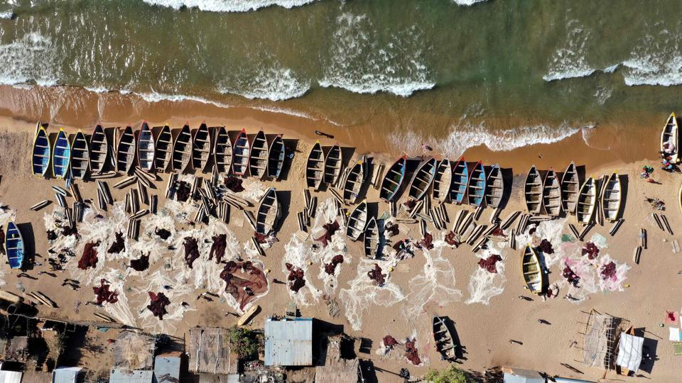 Fishing boats are seen on the shore of the Lake Malawi at the Senga village,in Senga, Malawi. A crowd eagerly awaits the arrival of a white and yellow cedar wood boat carrying its haul. (Gianluigi Guercia / AFP)