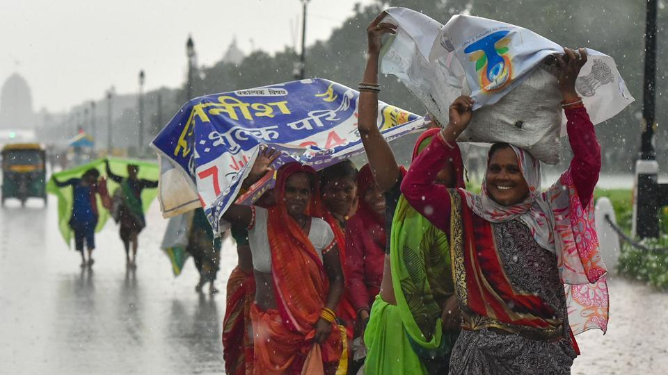 Women try to cover themselves with plastic banners as they walk along the Rajpath during rains, in New Delhi, Sunday, July 21, 2019.