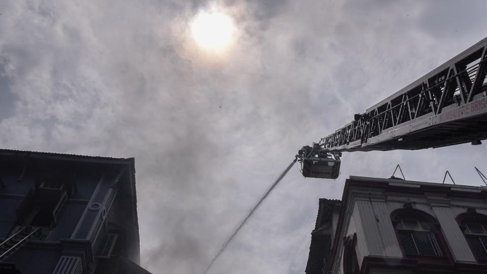 Firefighters attempt to douse a fire at Churchill Chambers near Taj Mahal Hotel, in Colaba, on Sunday.