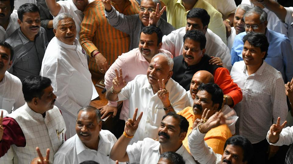Karnataka Bharatiya Janatha Party (BJP) leaders along with the party president B.S. Yediyurappa flash the victory sign after they were voted out of the ruling coalition government through a trust vote at the Vidhana Soudha, in Bangalore on July 23, 2019.