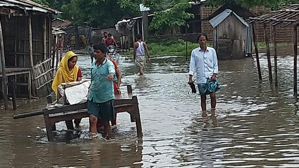 People struggle to move on a street flooded with water, in Araria, Bihar