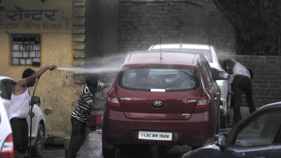 Man wash a car at a car-washing centre, in Noida, India.