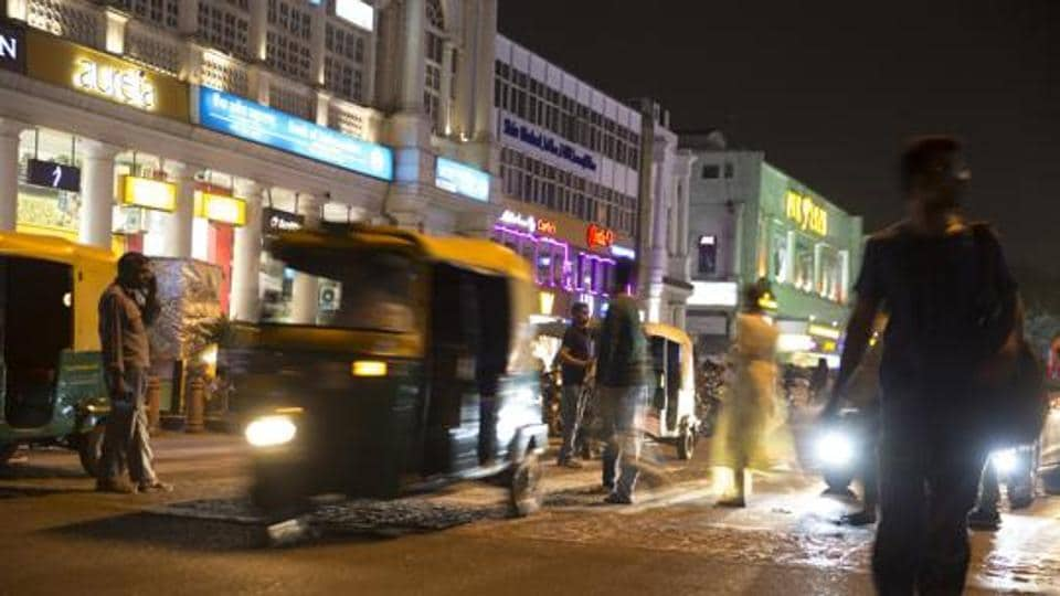 Pedestrians cross a road as auto-rickshaws travel past at Connaught Place in New Delhi. The GII ranks 129 world economies on 80 innovation indicators such as intellectual property filing rates, mobile app creation, education spending, and scientific and technical publications.