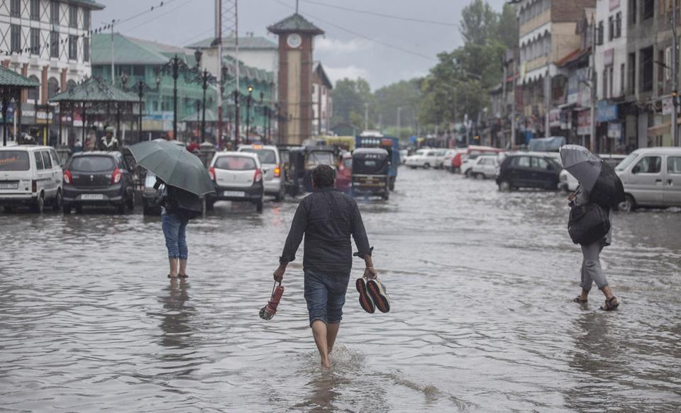 Jammu and Kashmir, July 25 (ANI): People walk in Waterlogged road after heavy rain in Srinagar on Thursday. (ANI Photo)