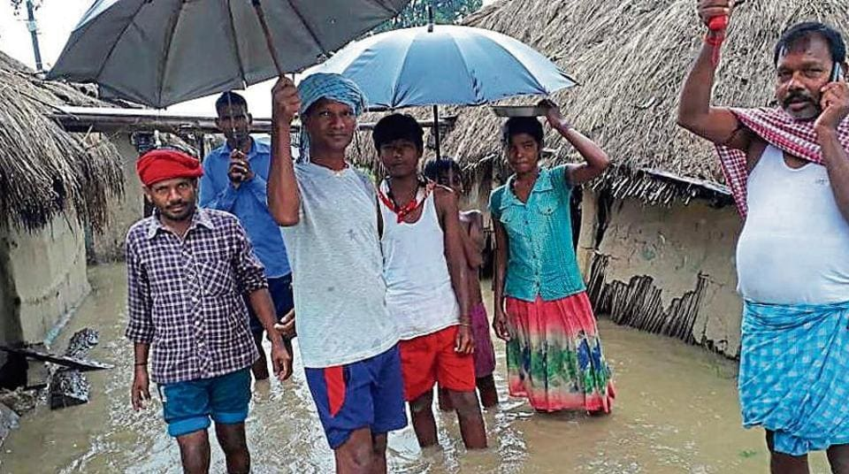 People wade in knee-deep water in West Champaran, Bihar.