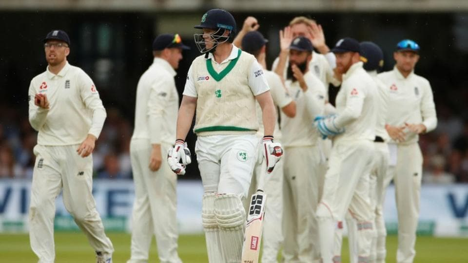 Ireland's Kevin O'Brien walks off as England players celebrate his dismissal by LBW.