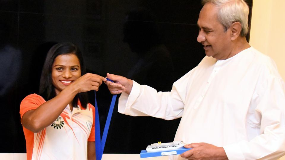Sprinter Dutee Chand shows Odisha Chief Minister Naveen Pattnaik the gold medal she won at World University Games.
