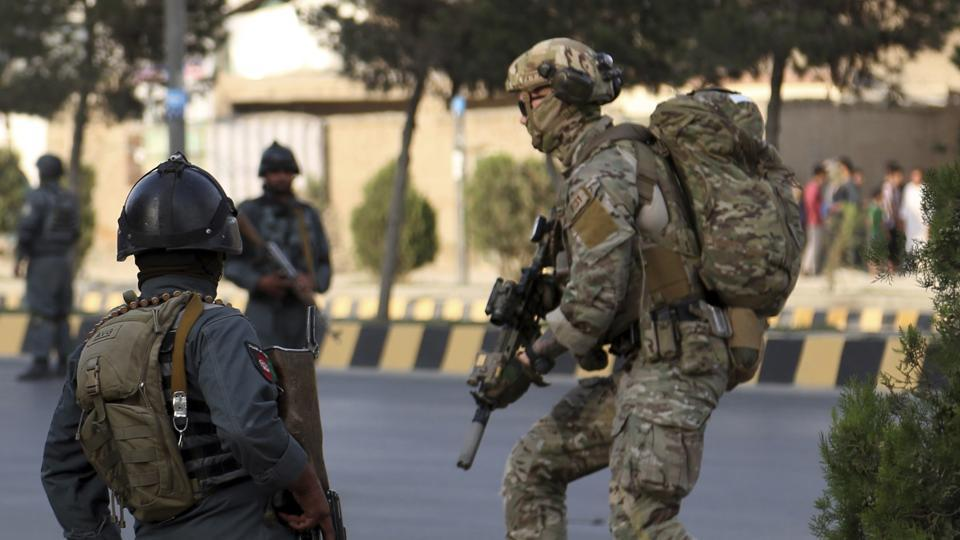 Afghan security personnel secure the site of an attack in Kabul, Afghanistan. Afghan officials say the political offices of the president's running mate were hit by a large explosion and stormed by an unknown number of attackers.