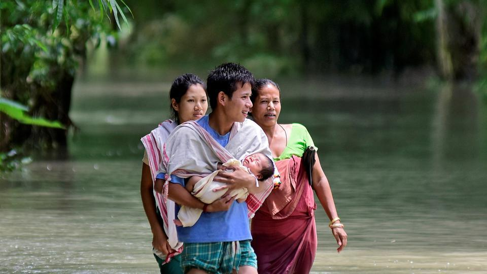 A man carries his new born baby as he and his family members wade through a flooded area to reach a relief camp at a village in Barpeta district of Assam, July 25, 2019.