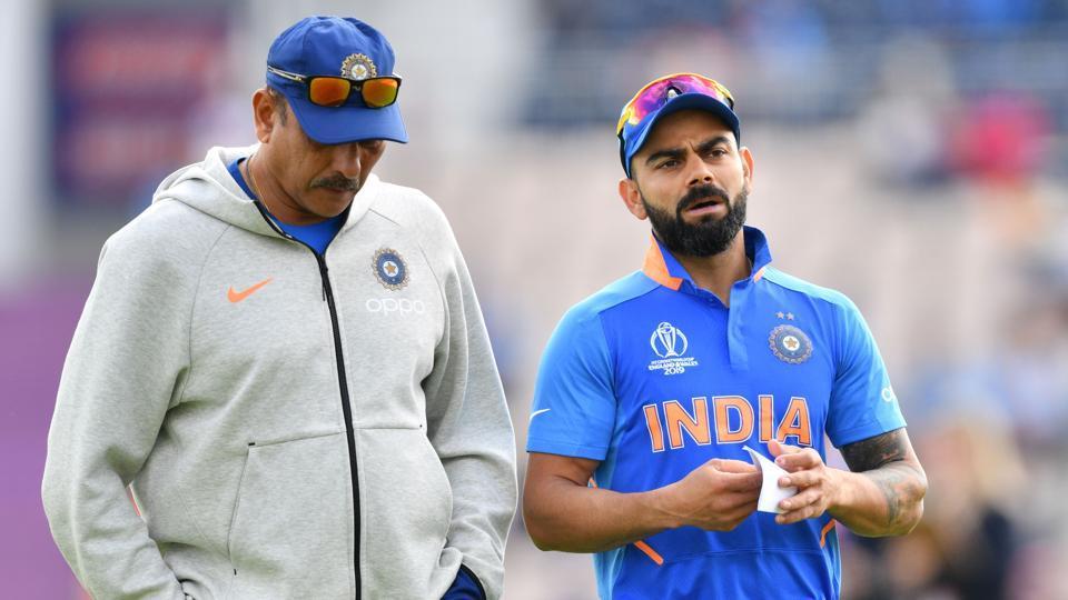 India's captain Virat Kohli (R) speaks with India's head coach Ravi Shastri.
