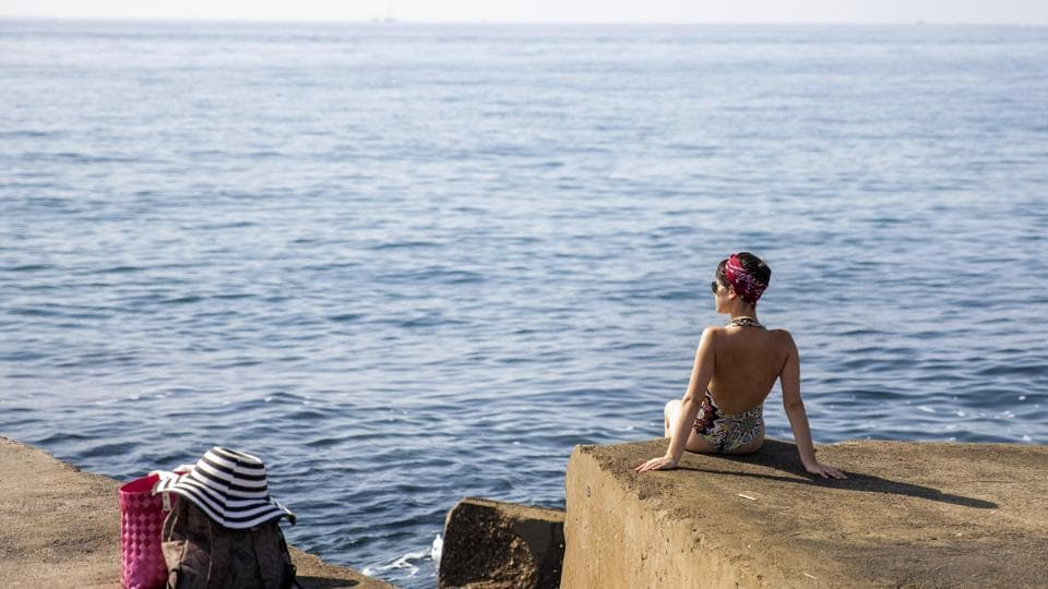 A woman sits on a breakwater in front of the Mediterranean sea in Barcelona, on July 25, 2019. Parts of Europe saw record-high temperatures on Thursday as much of the continent was trapped in a heat wave, the second in two months.