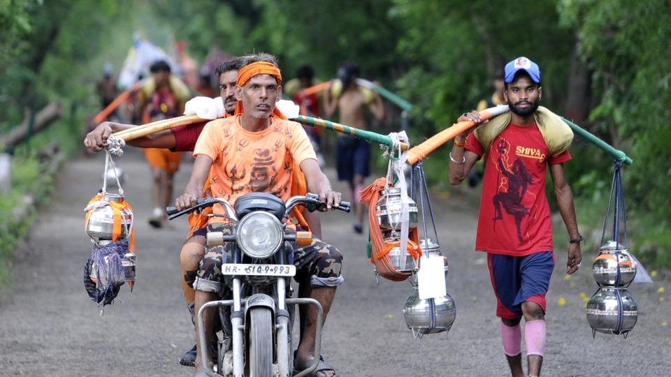 Kanwariyas seen on their way to Okhla Bird Sanctuary while coming back from Haridwar carrying water from the Ganga River, in Noida,  on Sunday, July 28, 2019.