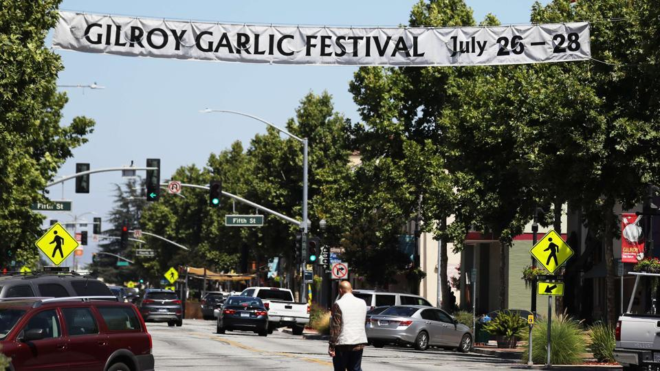 A man walks beneath a sign advertising the nearby Gilroy Garlic Festival after a mass shooting took place at the event on July 29, 2019 in Gilroy, California.