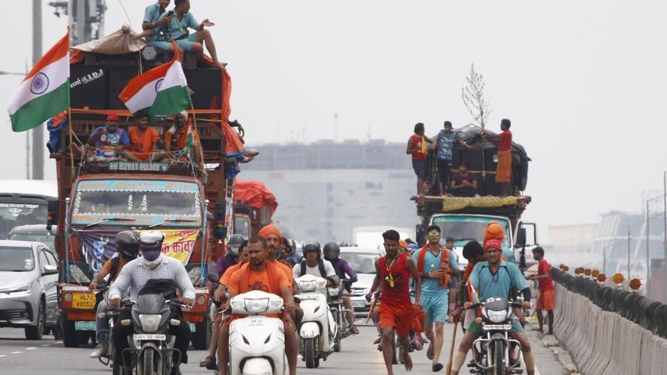 Kanwariyas carrying water from the Ganga River during the Kanwar Yatra ahead of Shivratri Festival, seen at Delhi- Gurugram expressway.