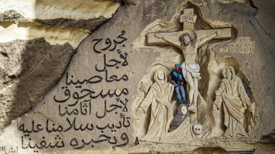 Artist Mario, sculptor of St. Simon the Tanner Monastery complex, poses for a picture alongside a scene relief depicting the Crucifixion of Jesus Christ and a verse in Arabic from the Biblical Book of Isaiah. Mario spent more than two decades carving the rugged insides of the seven cave churches and chapels of the rock-hewn St. Simon Monastery and church complex atop Cairo's Mokkatam hills, with designs inspired by biblical stories. (Mohamed el-Shahed / AFP)