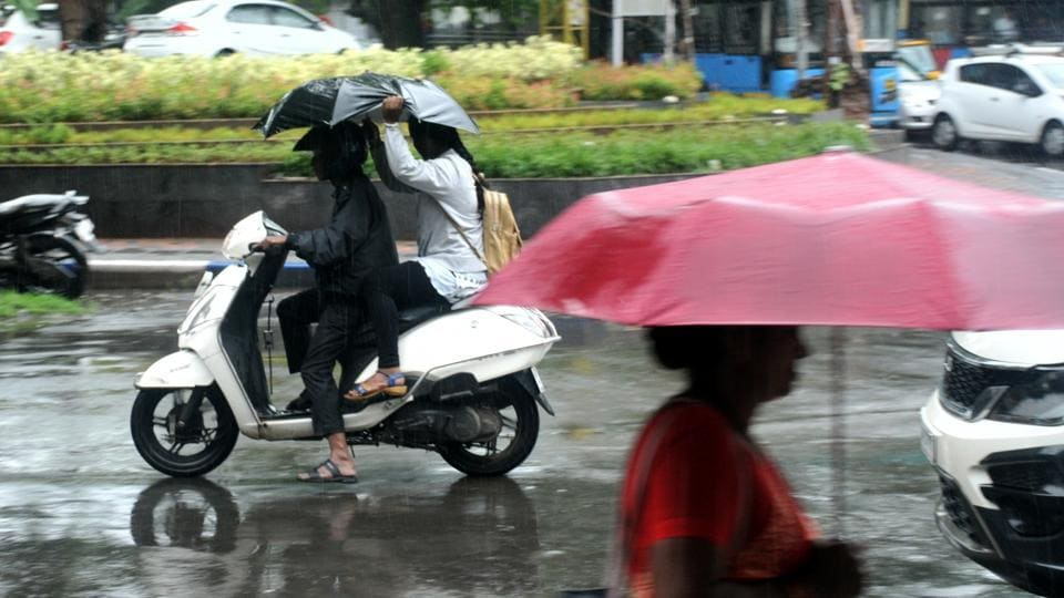 Commuters caught in the rain on Tilak road in Pune, India.