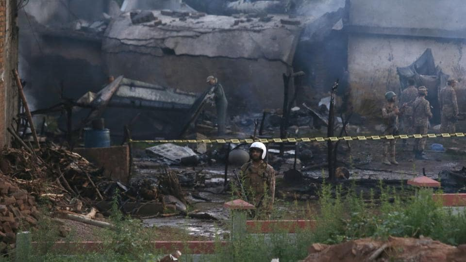 Pakistan army officials examine the site of a plane crash in Rawalpindi, Pakistan, Tuesday, July 30, 2019.